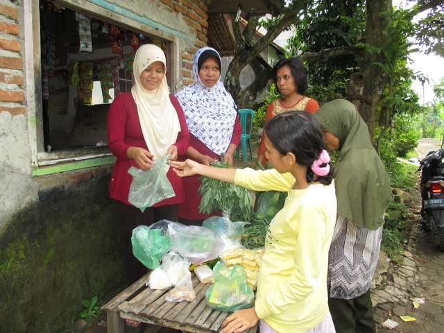 Supartini (Baju merah kerudung krem) sedang melayani tetangga yang belanja di warung sederhananya. Selain berjualan, Supartini aktif menjadi kader kesehatan reproduksi 'Aisyiyah di Cirebon