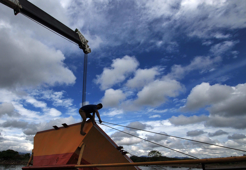 Warga dibantu crane menurunkan ponton untuk meletakkan bandul agar menghasillan energi listrik